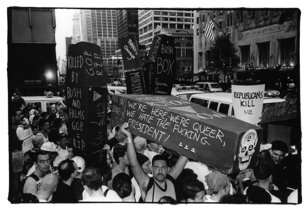 """A crowd of protesters fill a New York City street in 1990 during the height of the AIDS epidemic. The crowd holds up multiple coffins written with words like """"We're here, we're queer, we hate the fucking president!"""" and """"R.I.P. G.O.P."""""""