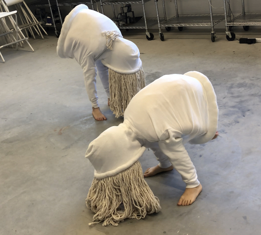 Poised in a grazing position on a concrete floor are what appear to be the upper halves of two people wearing white hoodies, except the arms are legs, and the hair falling to the floor appears to be the strands of a mop head.