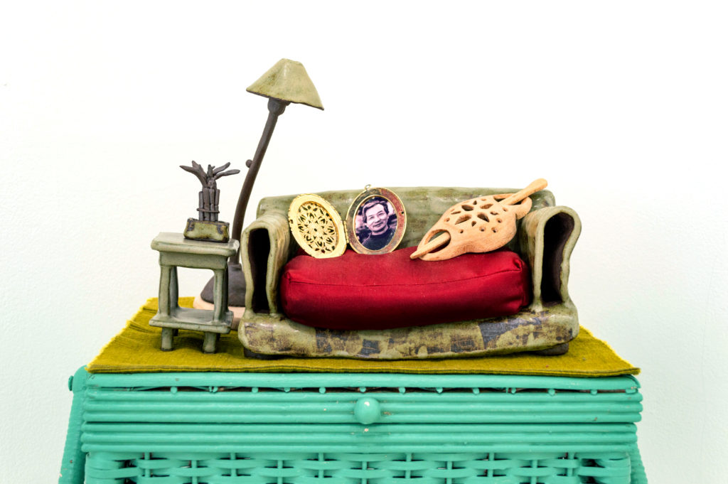 Placemat/rug, glazed ceramic miniature couch, side table, floor lamp, and lucky bamboo. Flax-seed-filled red cushion, brass locket, carved maple wood hair barrette.