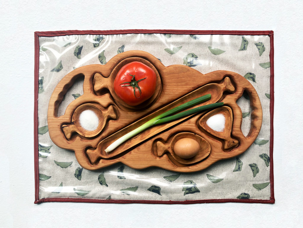 Oblong, rounded, wooden tray with handles on either side has indentations of various shapes. There are removable, spoon-like objects of the same material fitting just right into each of their respective places. The shape of each 'spoon' corresponds to and holds an ingredient used to make a commonly eaten, popular Chinese dish.