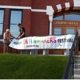 The banner for MNFF being set up in front of Middlebury's Town Hall Theater.