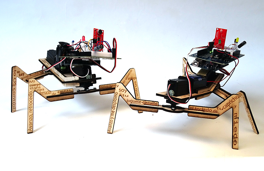 Two spider-like robots with bodies made of computer chips and wires and legs covered in Spanish words.