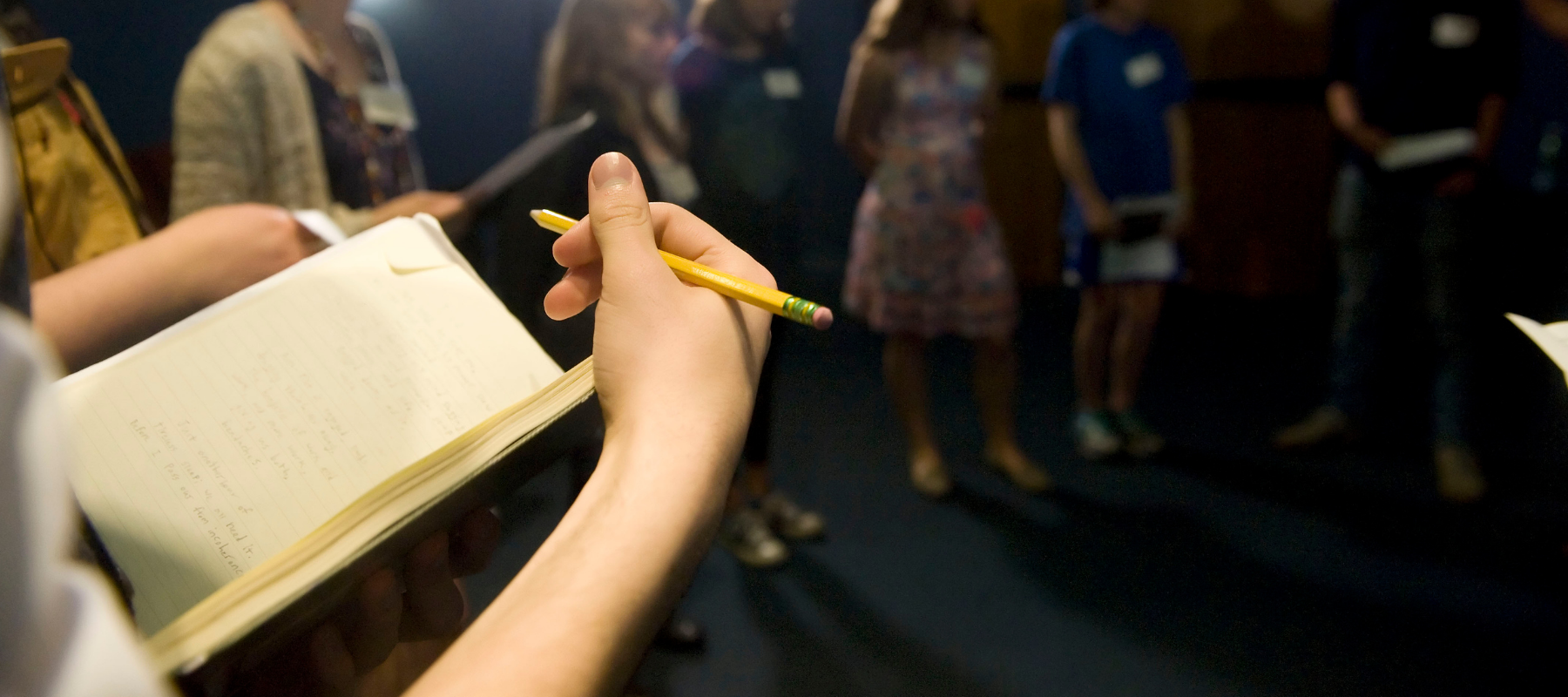 A close-up of someone's notebook as they hold a pencil over it with one hand.