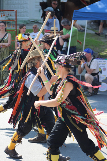 Morris dancers perform in costumes with feathers and streamers