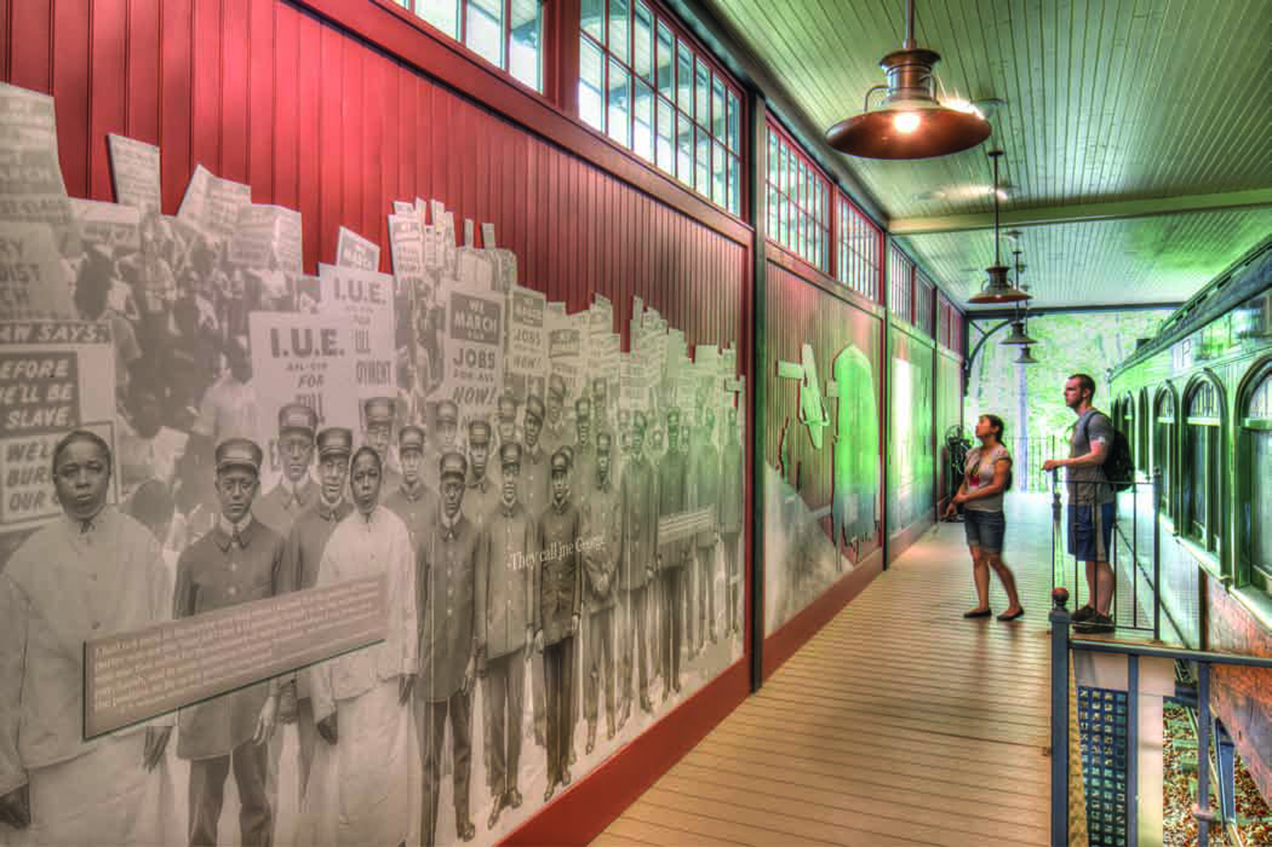 Two people stand in a long hallways viewing an exhibit about the Pullman porters on the wall.