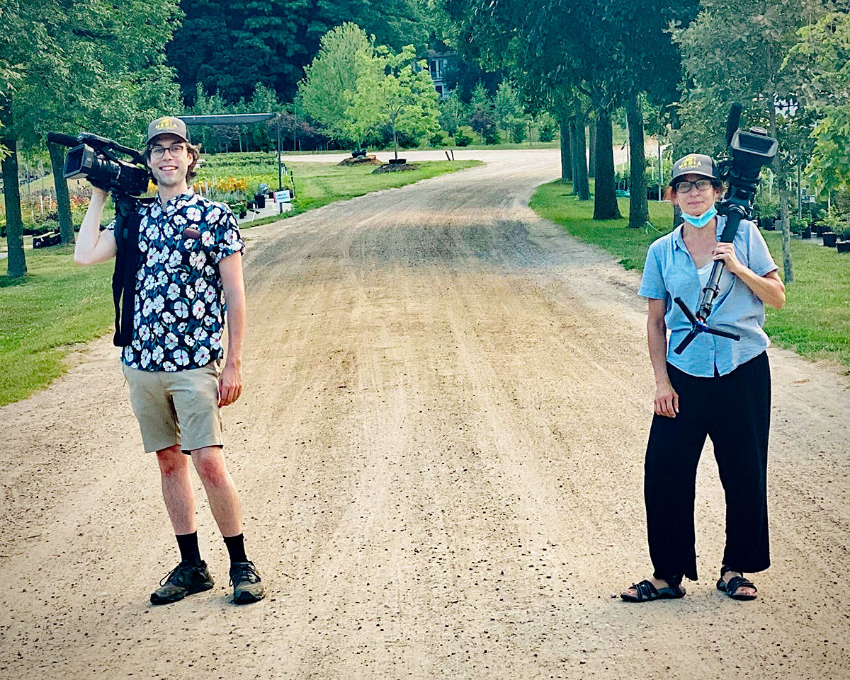 Two people holding camera equipment standing in a dirt road lined with trees.