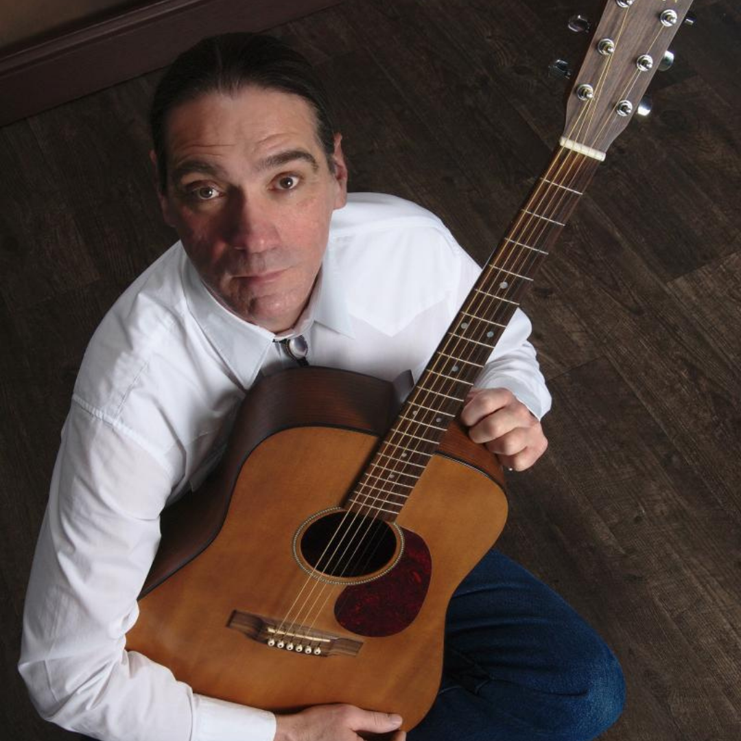Bryan Blanchette sitting cross-legged and cradling a guitar, looking into the camera.
