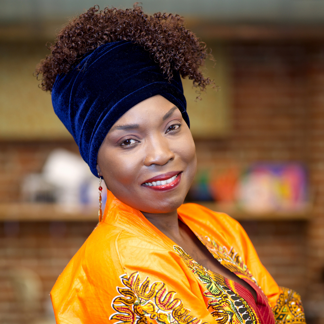 KeruBo seen from the shoulders up wearing orange silks and a blue velvet headwrap, smiling at the camera