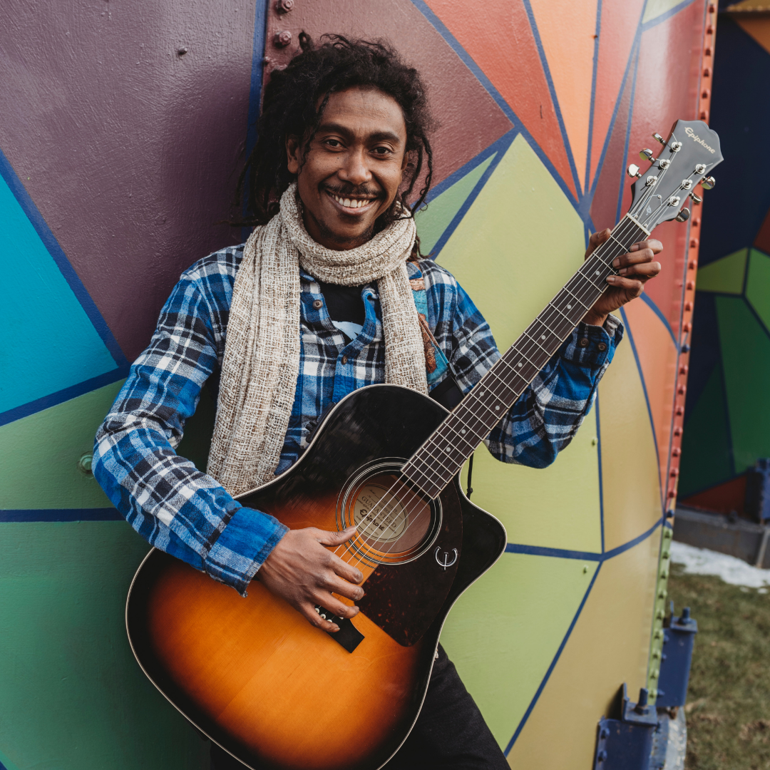 Mikahely leans against a colorfully painted wall, holding a guitar and smiling at the camera