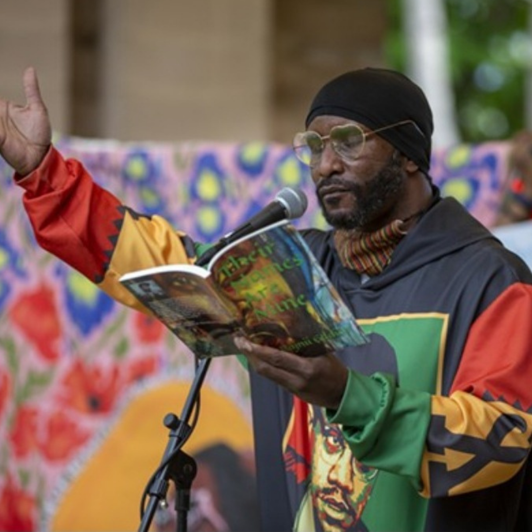 Rajnii Eddins reading from his book, Their Names Are Mine, at a microphone in Battery Park in Burlington, VT