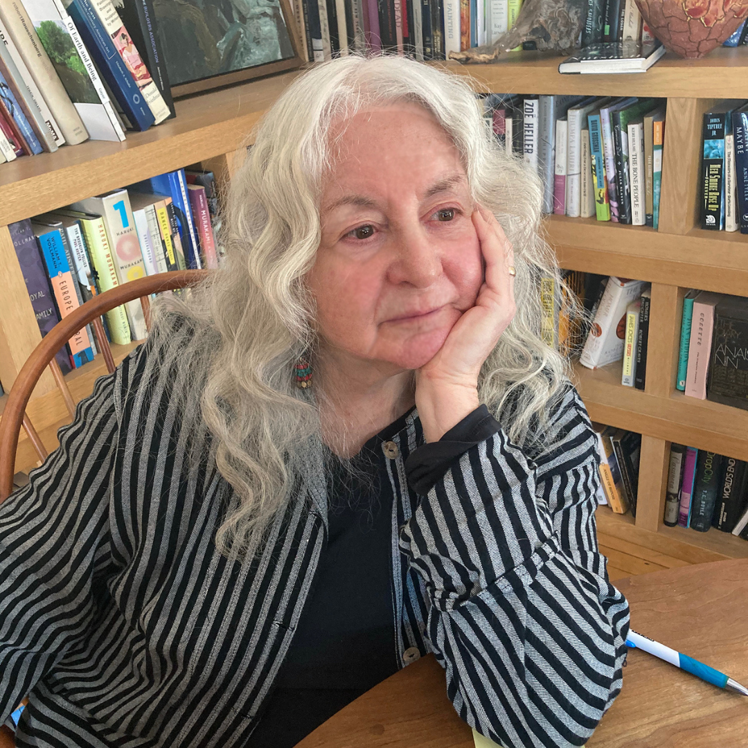 Riki Moss sitting at a table with bookscases behind her, resting her chin in her hand and looking off camera