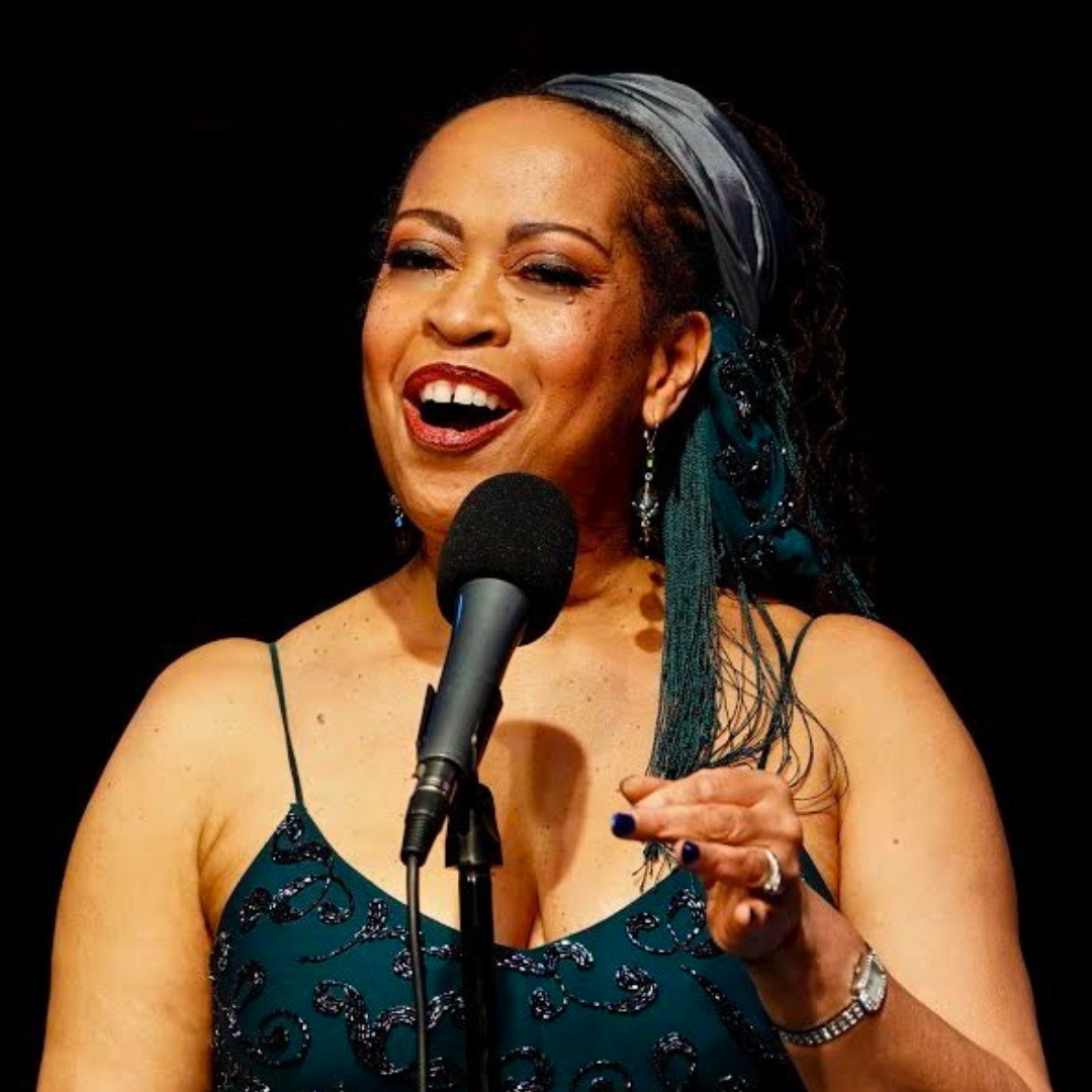 Samira Evans seen from the shoulders up, singing behind a microphone.