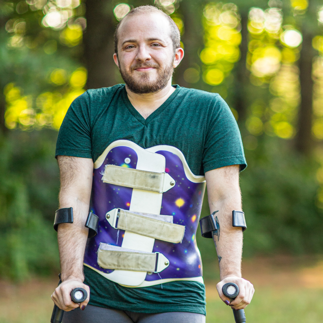 Toby MacNutt standing with forearm crutches and a back brace, smiling at the camera with trees behind them