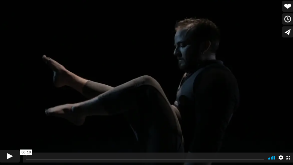 Toby MacNutt performs against a black backdrop, seated with legs raised in a cycling positions