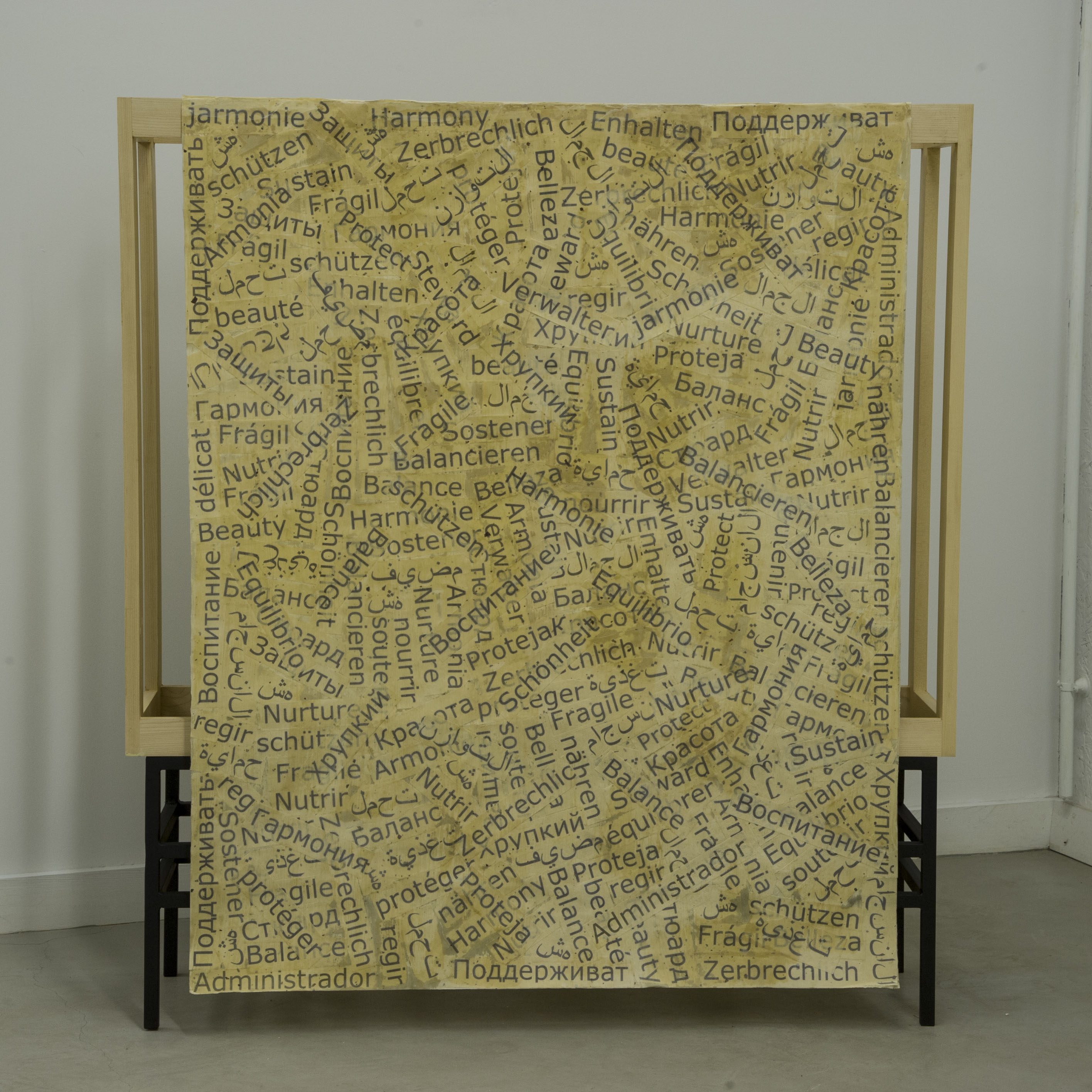 Comfort by Pat Musick, a large sheet of paper covered in words, displayed on a loom-like structure