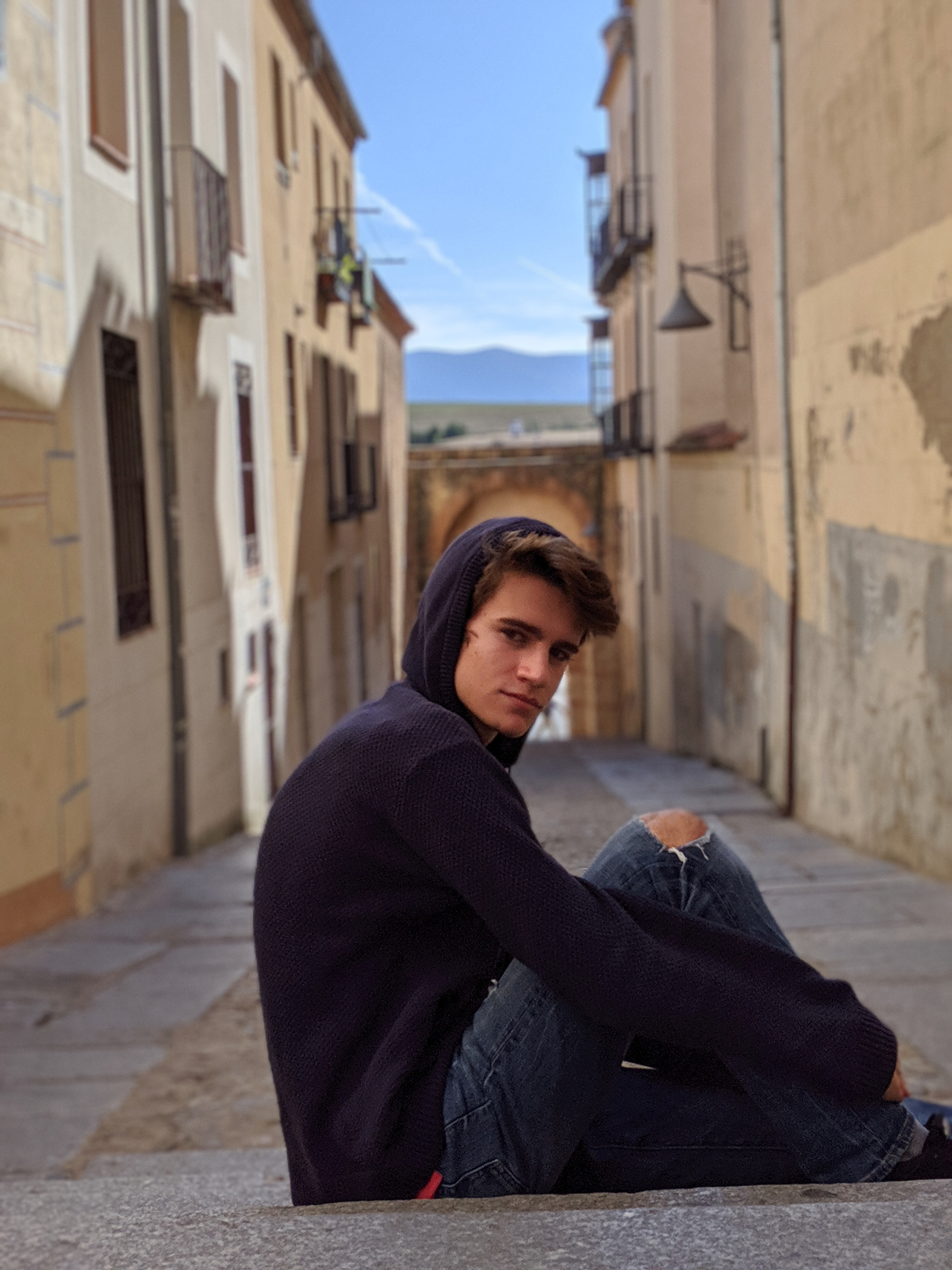 Beniamino Nardin seen sitting in a cobbled street with his knees to his chest, looking at the camera