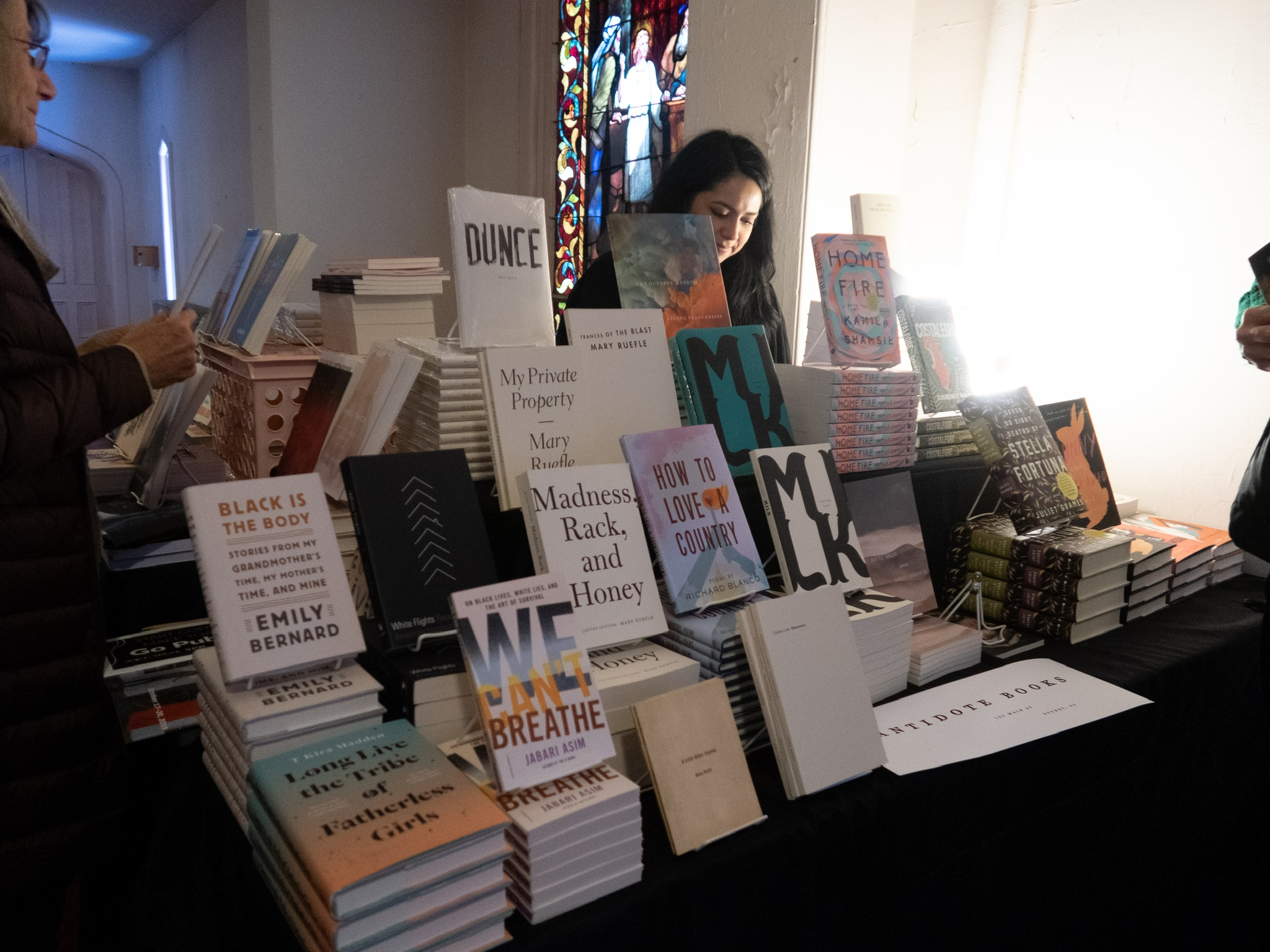 Books arranged on a table with shoppers browsing them at the 2019 Brattleboro Literary Festival