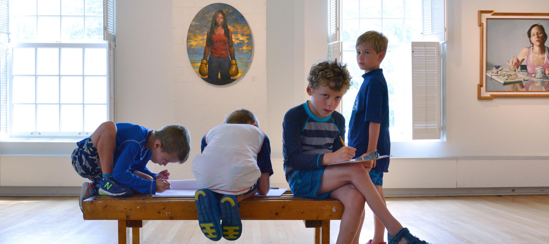 Children writing on clipboards in an art gallery.