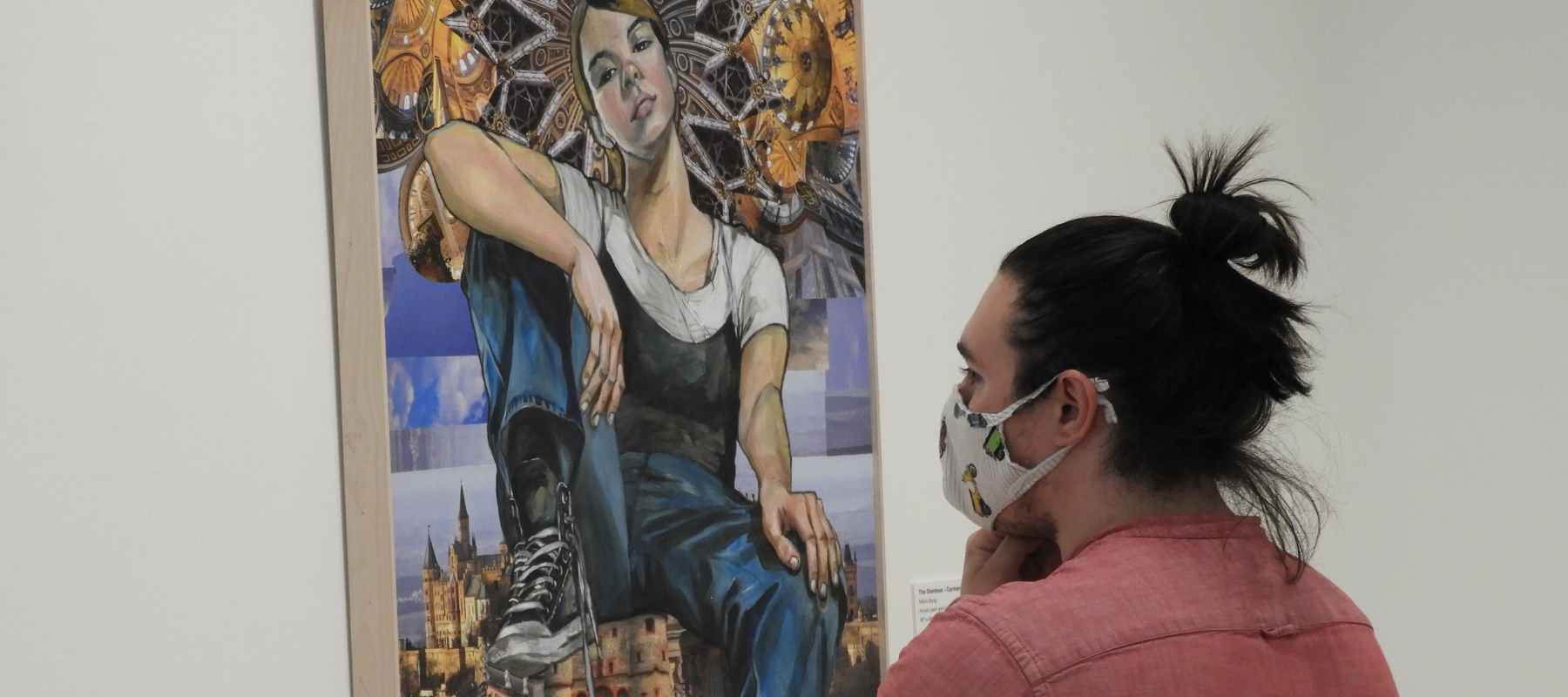 A person wearing a face mask views a painting on a gallery wall.