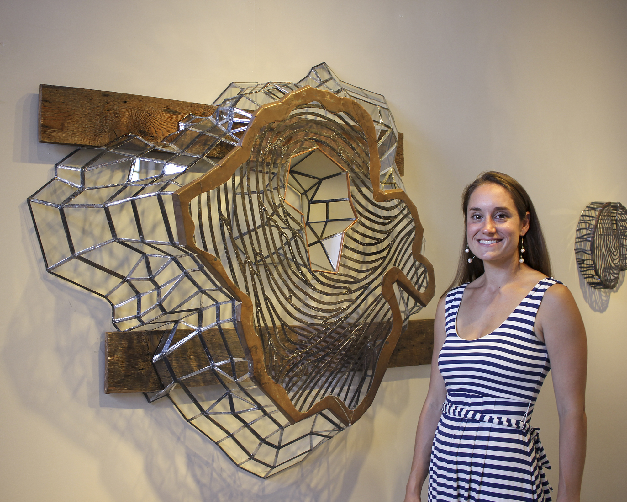 Stefania Urist stands by one of her sculptures mounted on a wall