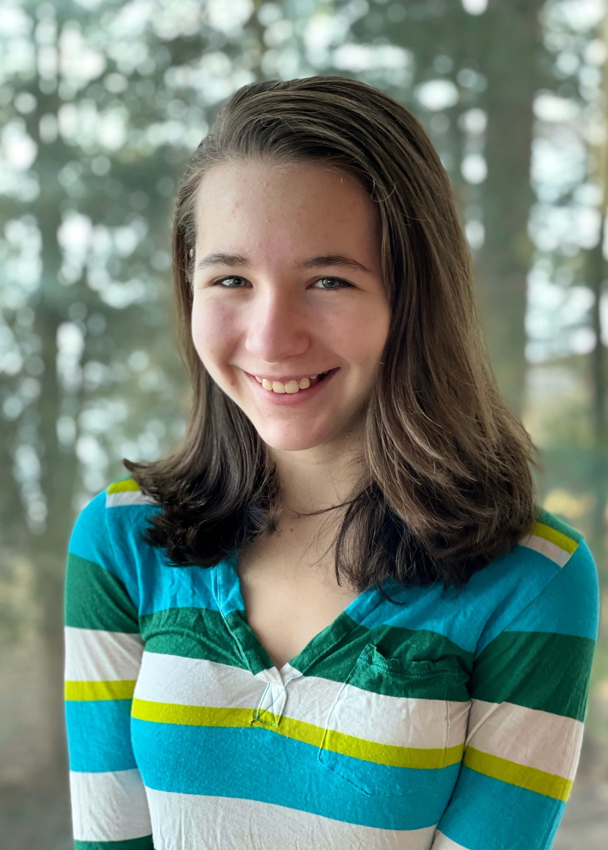 Talia Gibbs seen from the chest up, smiling at the camera with trees in the background.